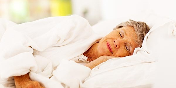 Elderly woman sleeping on a bed.