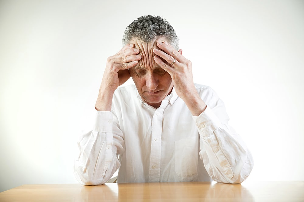 Elderly man with stress and a headache.