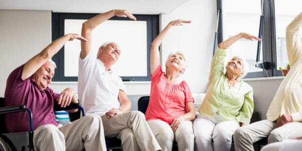 A group of elderly people enjoying an exercise class while being able to be seated.