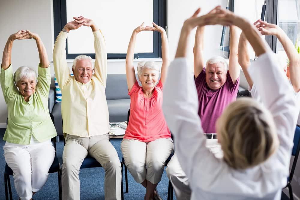 A group of elderly people enjoying an exercise class seated.