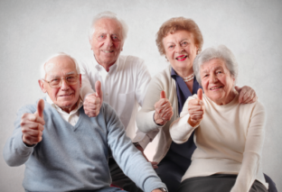 Elderly people with their thumbs up.