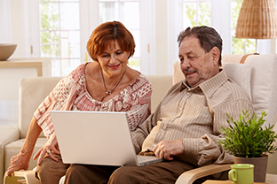 Elderly couple using laptop computer at home.