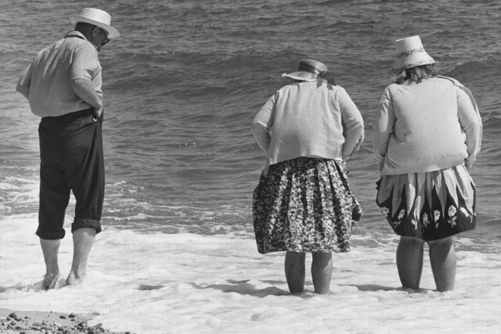 Holidaymakers padding in the sea