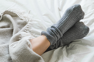 Feet in grey socks on a bed with a cosy blanket.