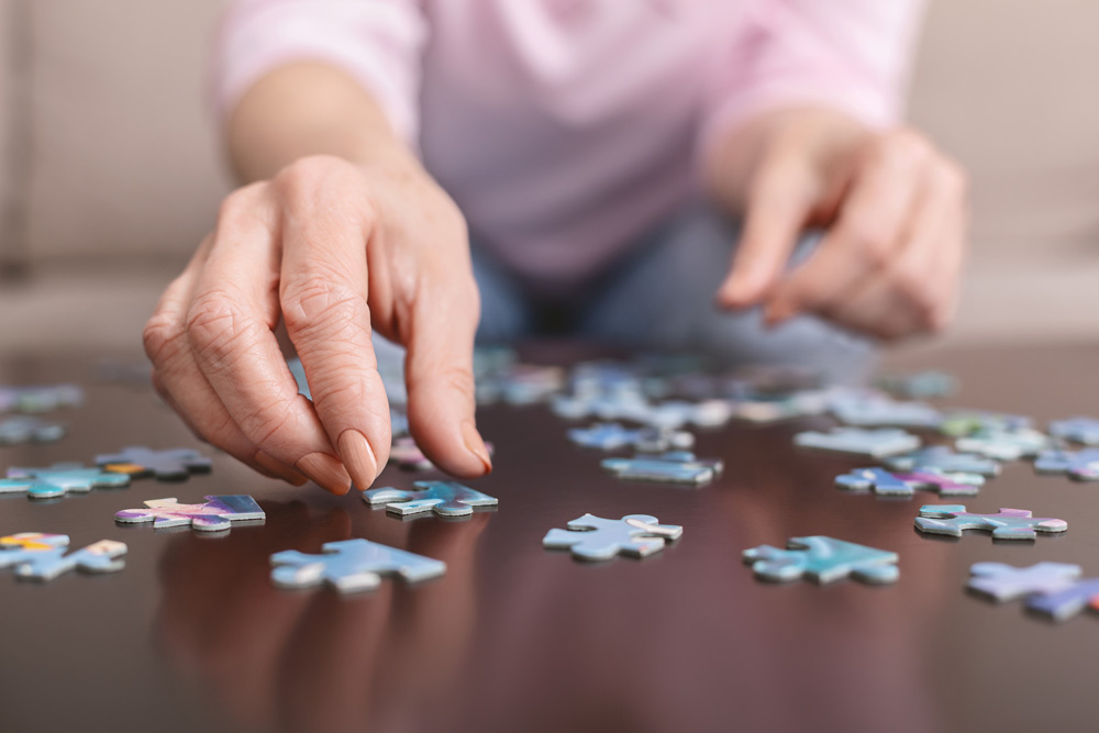 Elderly woman with dementia doing a puzzle.