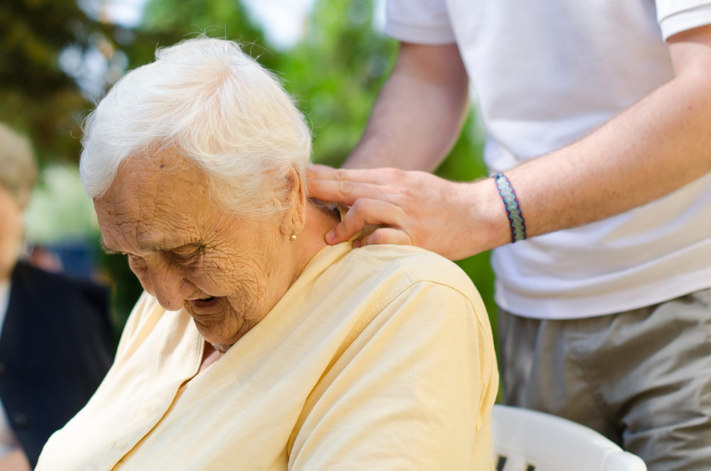 Old woman receiving a neck massage