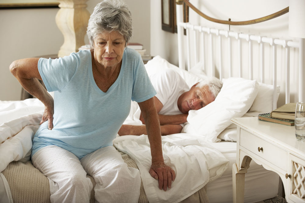 Elderly lady with back pain getting out of bed