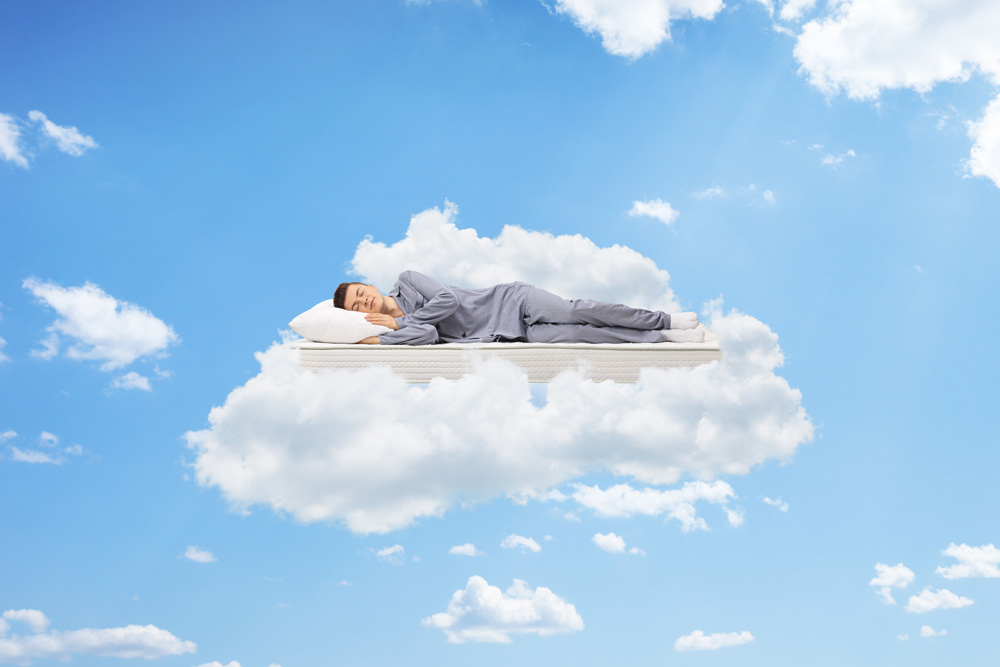 A man relaxing on a mattress in the clouds