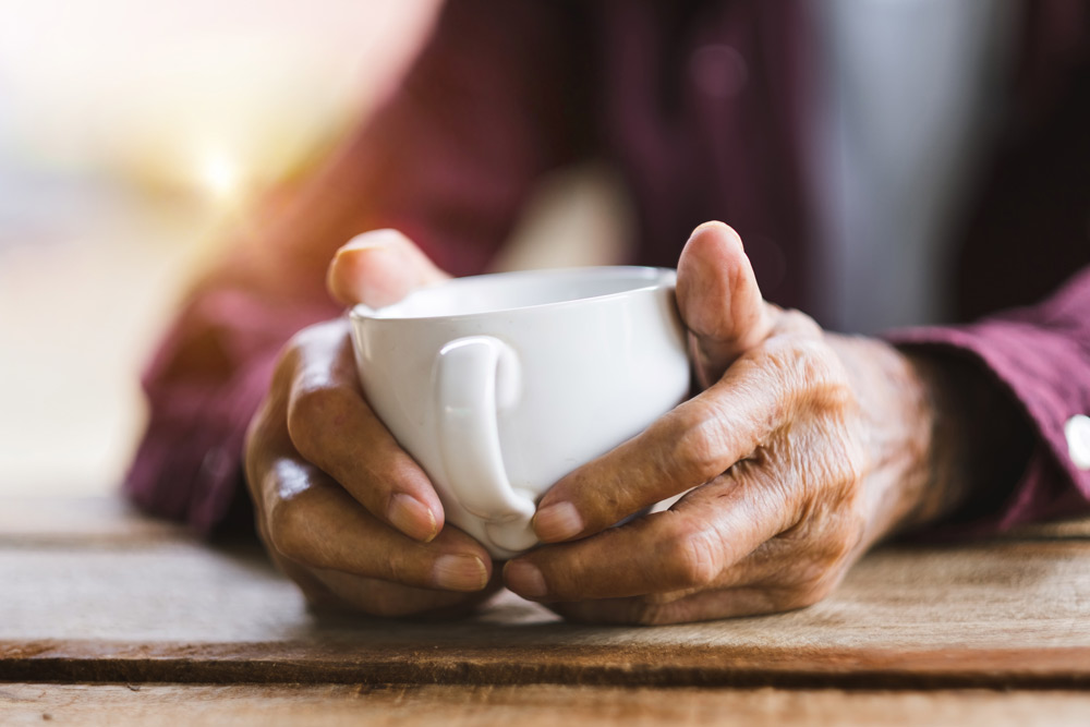 Elderly person holding a cup of coffee