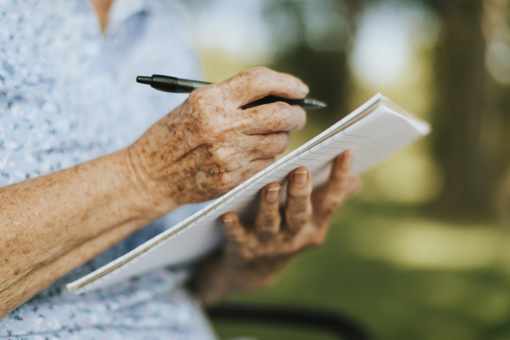 Elderly person taking notes in a journal