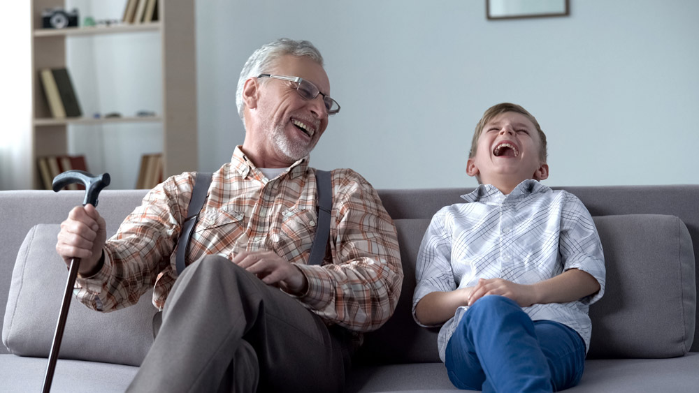 Elderly man laughing and spending time with his grandson to relieve stress