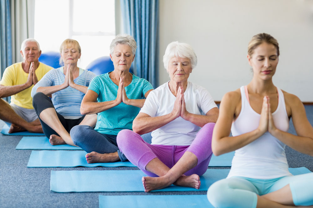 Elderly people taking a yoga class and being mindful to relieve stress